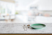 Empty round green ceramic dish on marble counter in blurred kitchen background. For food and product display montage.