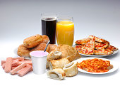 A selection of processed food and drink on a white background including pIzza, cola, buscuits and sausage rolls