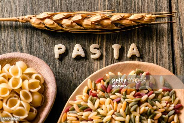 Food sign of Italian pasta over rustic wooden table. Colored Orzo pasta in a wooden spoon.