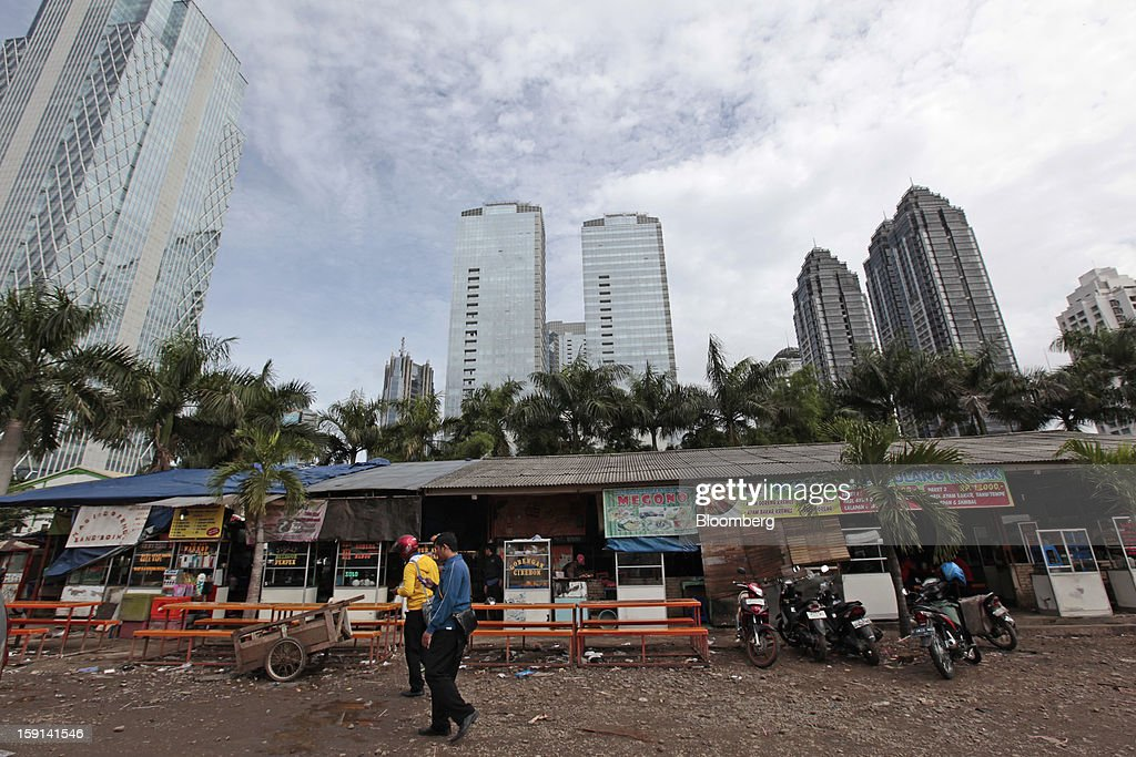 Food stalls stand in front of buildings in the financial district of Jakarta, Indonesia, on Tuesday, Jan. 8, 2013. Indonesia's rupiah weakened by the most in six months on concern the government's failure to meet its spending target last year will hamper economic growth and damp demand for local assets. Photographer: Dimas Ardian/Bloomberg via Getty Images