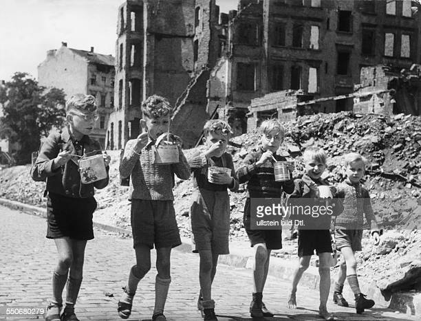 Food supply in Berlin after the war Boys eating their school lunch from tin cans in ther streets in the background ruins and rubble