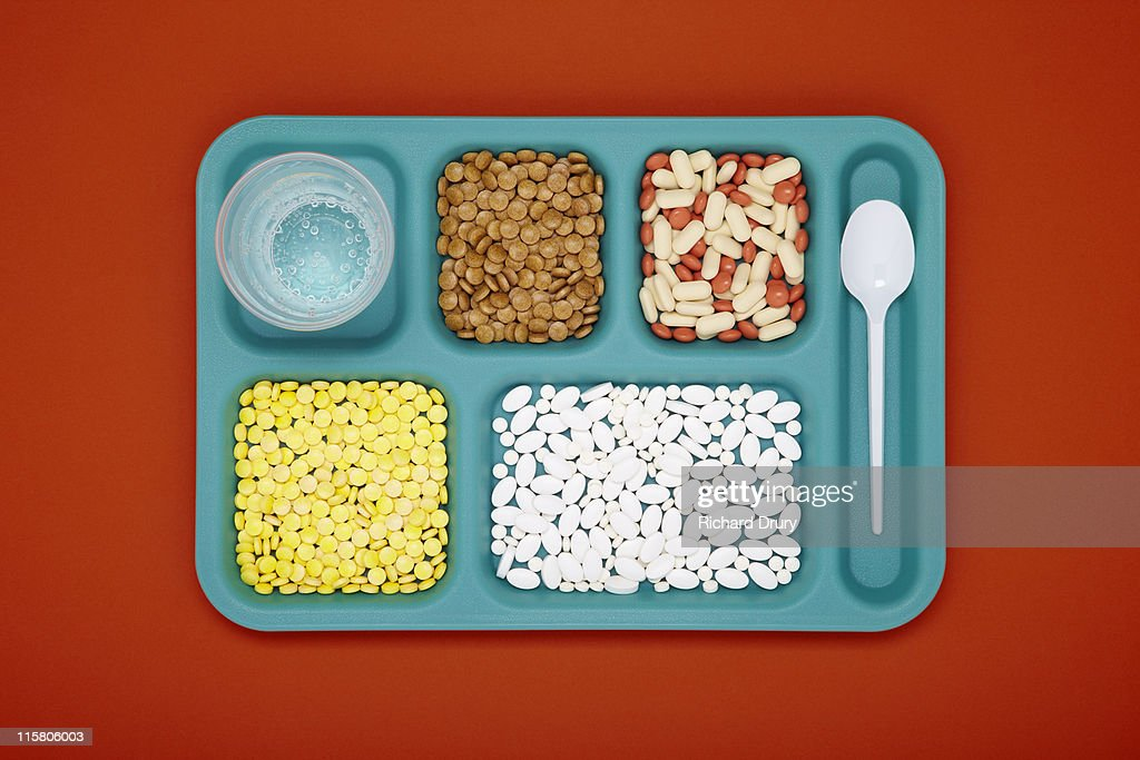 Food tray with vitamin pills, spoon and cup : Stock Photo