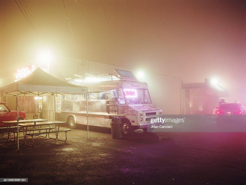 Food truck on parking lot in fog , police car in background.