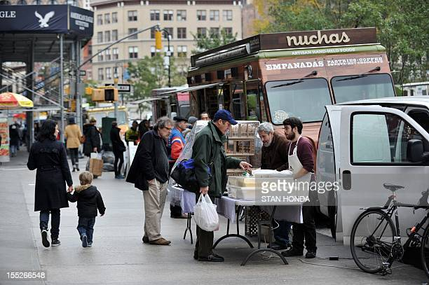 Food trucks and men selling bread and cheeses line Broadway at Union Square November 2 2012 in New York as the city recovers from the effects of...