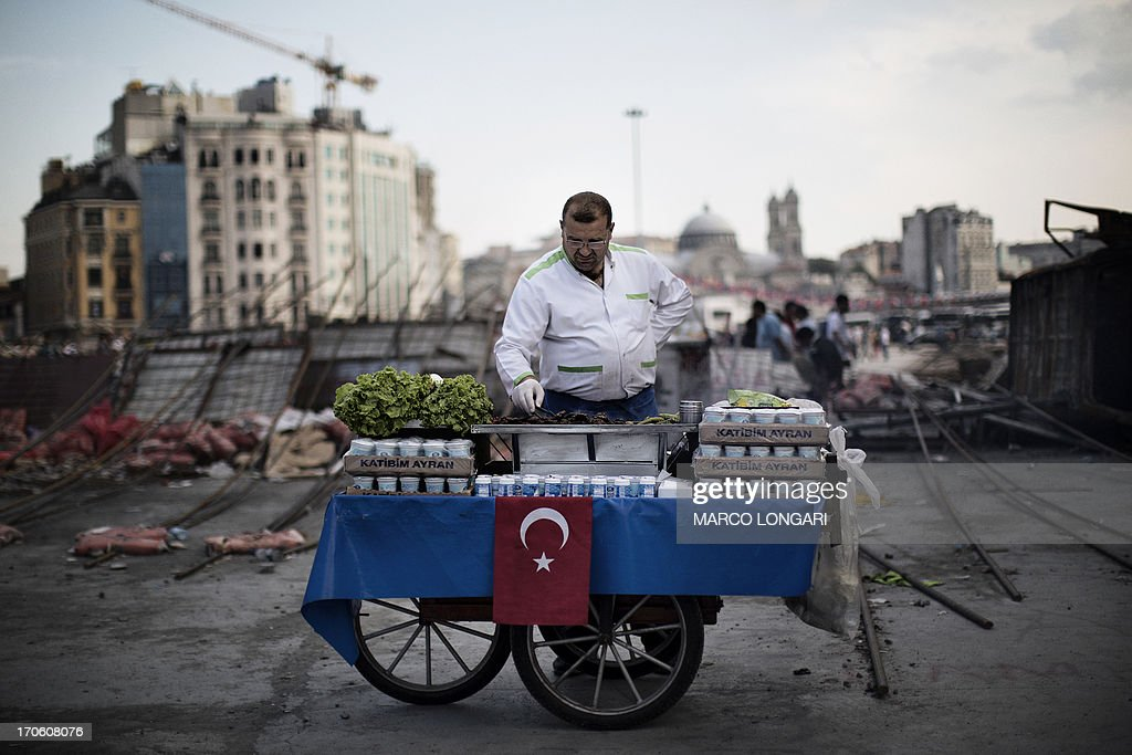 A food vendor grills meet on his cart in Istanbul's Taksim square, on June 15, 2013. Turkish protesters today refused to budge from an Istanbul park at the centre of nationwide anti-government demonstrations after rejecting a government olive branch aimed at ending two weeks of deadly unrest. The government said it would 'make an evaluation' after protesters rebuffed Prime Minister Recep Tayyip Erdogan's promise to halt the redevelopment of Gezi Park, saying their movement was bigger than a conservation struggle.