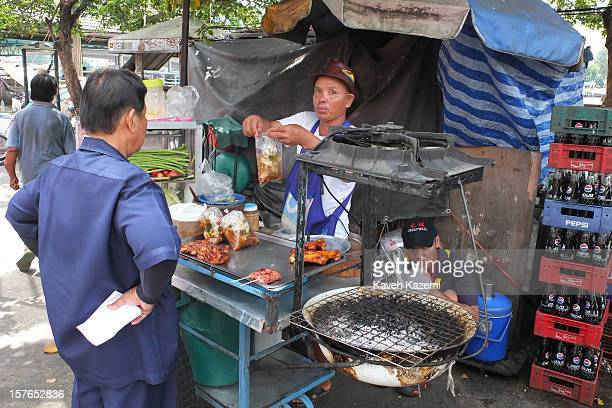 A food vendor hands a plastic bag containing food on the street on October 25 2012 in Bangkok Thailand