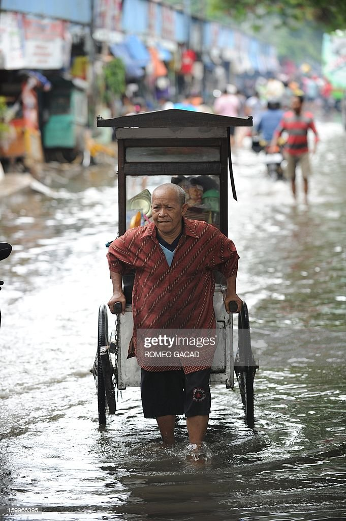 A food vendor pulls his cart on a flooded neighborhood in Jakarta on January 24, 2013. Indonesia's National Disaster Mitigation Agency (BNPB) said more than 30,000 people were displaced while 20 people died during the widespread flooding that hit Jakarta as the weather bureau forecast more rains in the coming days.