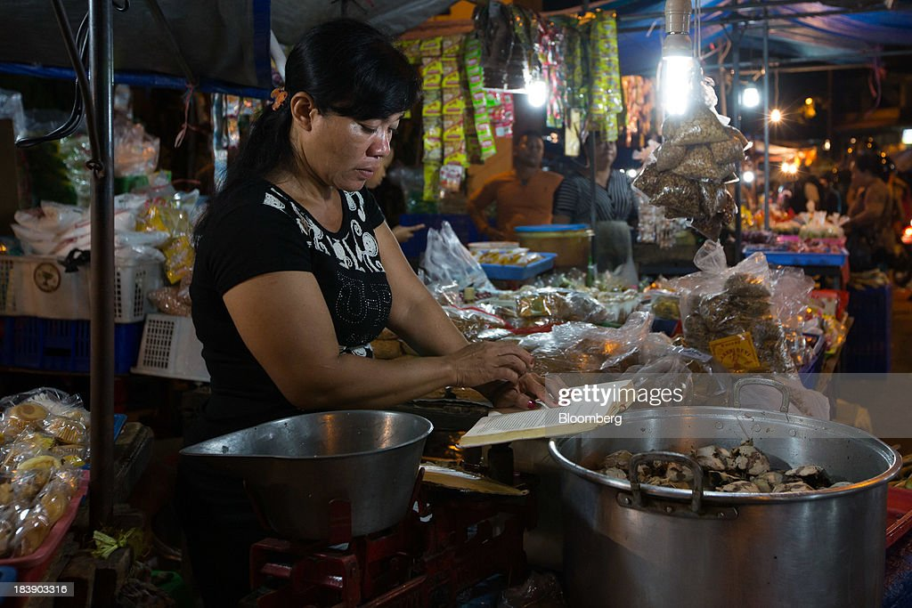 A food vendor reads a book as she waits for customers at the Pasar Badung market in Denpasar, Bali, Indonesia, on Tuesday, Oct. 8, 2013. Bank Indonesia said it will regulate currency hedging by individuals and companies, including state-owned firms, to help stabilize Asias most-volatile currency. Photographer: SeongJoon Cho/Bloomberg via Getty Images