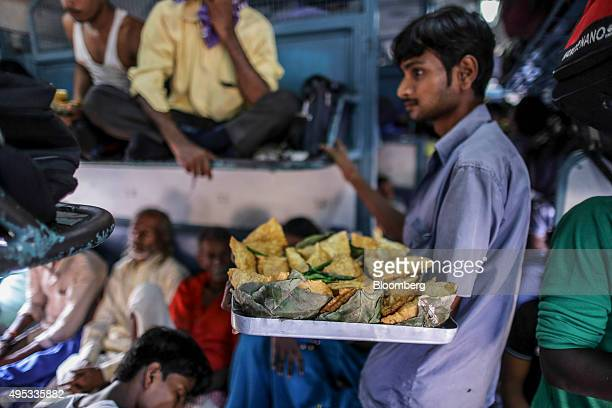 A food vendor sells snacks on the Kalka Mail train while traveling from Fatehpur station to Allahabad Junction station near Fatehpur Uttar Pradesh...