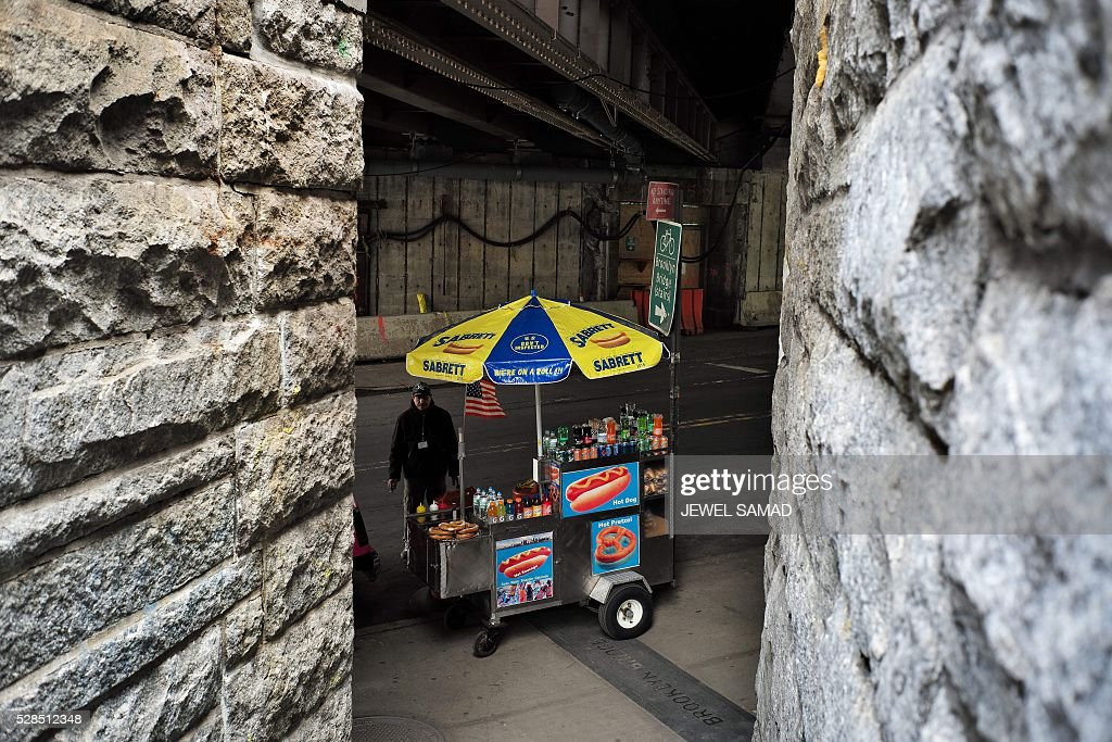 A food vendor waits for customers near the Brooklyn Bridge in New York on May 5, 2016. / AFP / Jewel SAMAD
