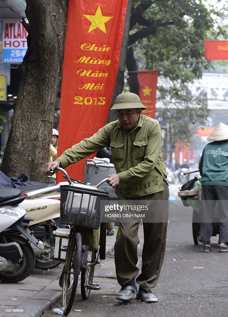 A food vendor walks past a red banner marking the 2013 new year in downtown Hanoi on December 28, 2012. Vietnam's economic growth slowed to the weakest pace in 13 years in 2012, according to published official statistics, piling more pressure on the country's rulers. Gross domestic product grew by 5.03 percent this year while inflation slowed to 6.8 percent in December year-on year from 7.08 percent in November. AFP PHOTO/HOANG DINH Nam