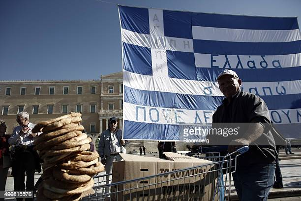 A food vendor wheels a trolley past trade unionists protesting outside the Greek parliament on Syntagma Square during a 24 hour general strike in...