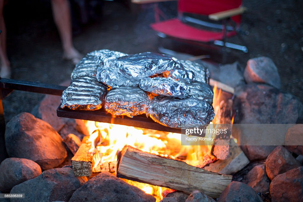 Food wrapped in tin foil cooking over campfire