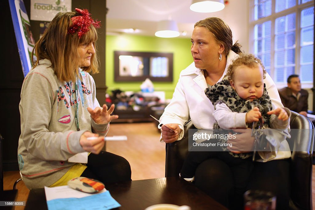 Foodbank volunteer Linda Wilson (L) talks to Elaine Oliver and her daughter Safiyah Lesley, aged 14 months, after collecting essential Christmas food on December 21, 2012 in Liverpool, England. Elaine, who is a mother of five, had her home burgled this week and had all of the children's Christmas presents and family housekeeping money stolen and had to turn to the Foodbank to help them through Christmas. With Christmas only days away, volunteers at the Central Liverpool Foodbank at the Frontline Trust, have seen one of their busiest days of the year as they give out free food for the needy. The centre has been giving out festive treats as well as its normal food donation - feeding over 1000 individuals in its first year, including over 300 children..
