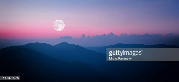Faire le bouffon lune montante au-dessus de la chaîne de montagnes