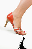 Foot in high heels stepping on crack