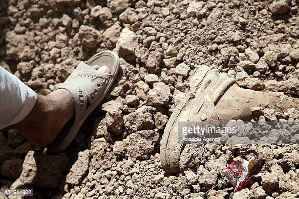 A foot of a victim sticks out from the rubble as the search and rescue works are going on at the site of an accident after city wall collapsed in...