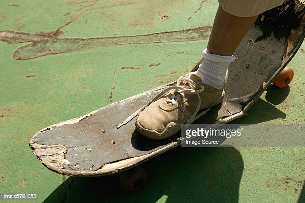 Foot on broken skateboard