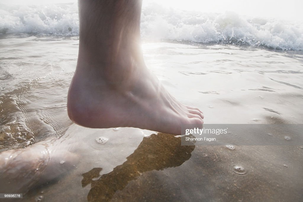 Foot steping into water at beach : Stock Photo