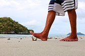 Image of the foot is stepping on broken glass bottles on the beach.