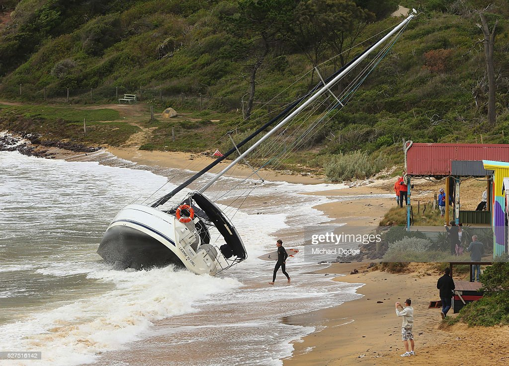 A 40 foot yacht is washed to the shore from its mooring as a surfer makes the most of rare waves at Shire Hall beach near Mornington Harbour on May 3, 2016 in Melbourne, Australia. Wind gusts of up to 100km per hour are expected in Melbourne and parts of southern Victoria as part of a deep cold front moves across the state.