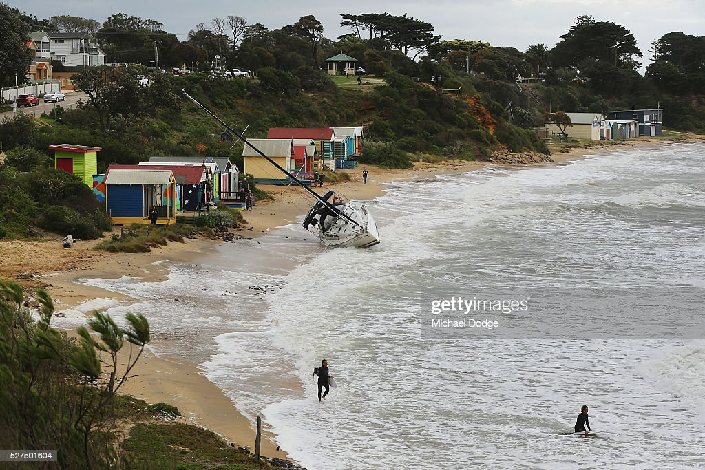 A 40 foot yacht is washed to the shore from its mooring as surfers make the most of rare waves at Shire Hall beach near Mornington Harbour on May 3, 2016 in Melbourne, Australia. Wind gusts of up to 100km per hour are expected in Melbourne and parts of southern Victoria as part of a deep cold front moves across the state.
