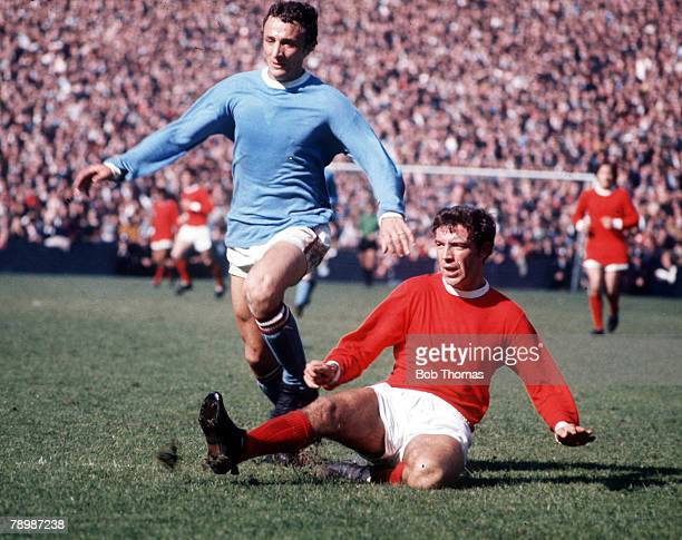 Football 1960's Manchester City's Mike Sumerbee is challenged for the ball by Manchester United's Dave Sadler during the derby match