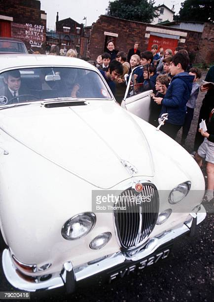 Football 1960's Manchester United star George Best gets out from a white Jaguar car surrounded by a group of autograph hunting children as he arrives...