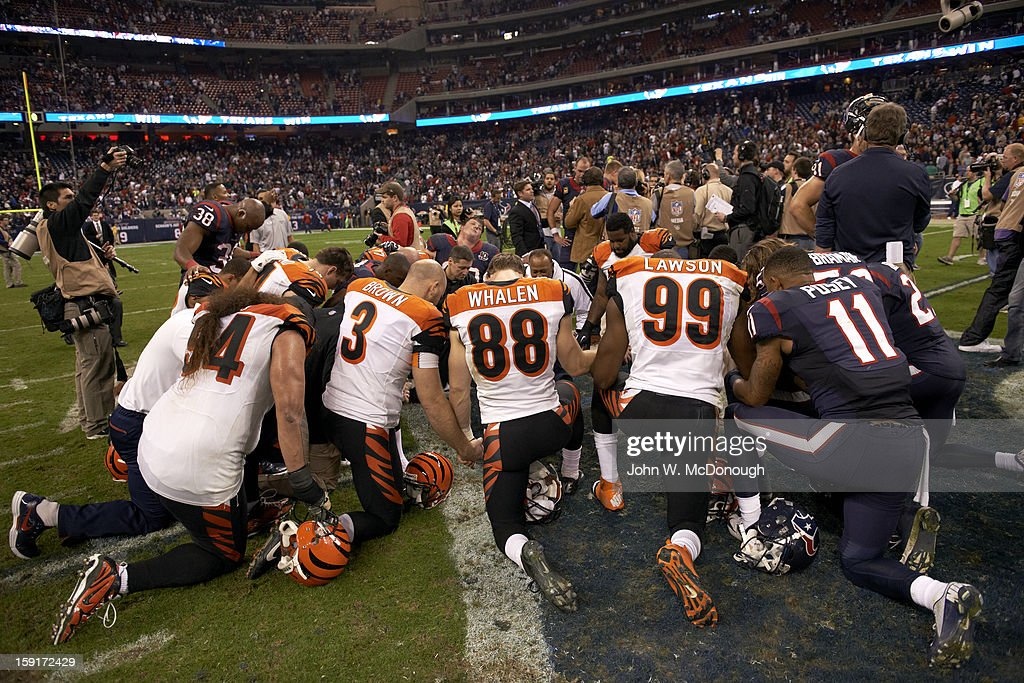 View of Houston Texans and Cincinnati Bengals players kneeling on field in prayer after game at Reliant Stadium. John W. McDonough F29 )