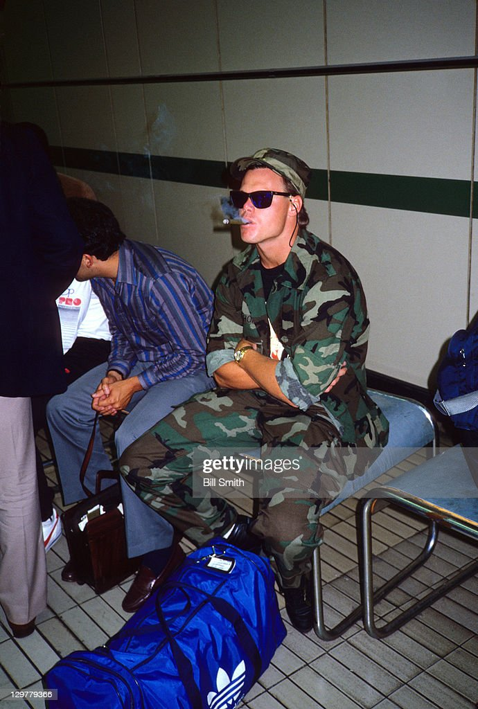 Chicago Bears QB <a gi-track='captionPersonalityLinkClicked' href=/galleries/search?phrase=Jim+McMahon+-+American+Football+Player&family=editorial&specificpeople=228299 ng-click='$event.stopPropagation()'>Jim McMahon</a> (9) wearing Camouflage and smoking cigar while sitting in customs at Heathrow Airport in Hillingdon. Bill Smith F33 )