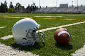 Football and football helmet on football field