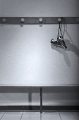 Football boots hanging in change room (B&W)