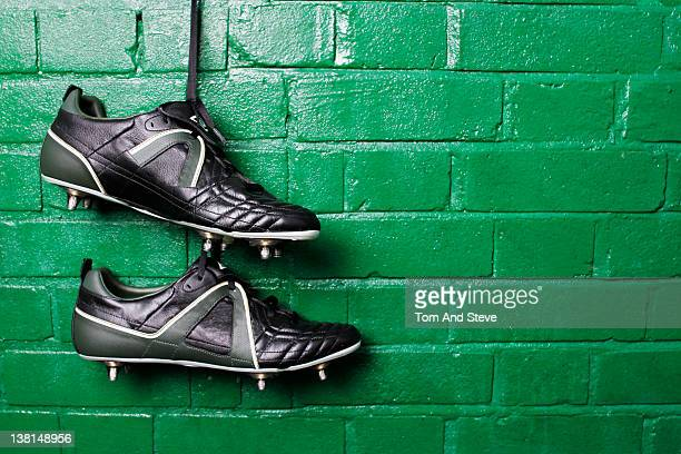 Football boots hanging in changing room wall.