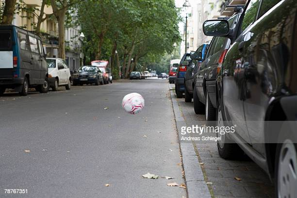 A football bouncing across the street