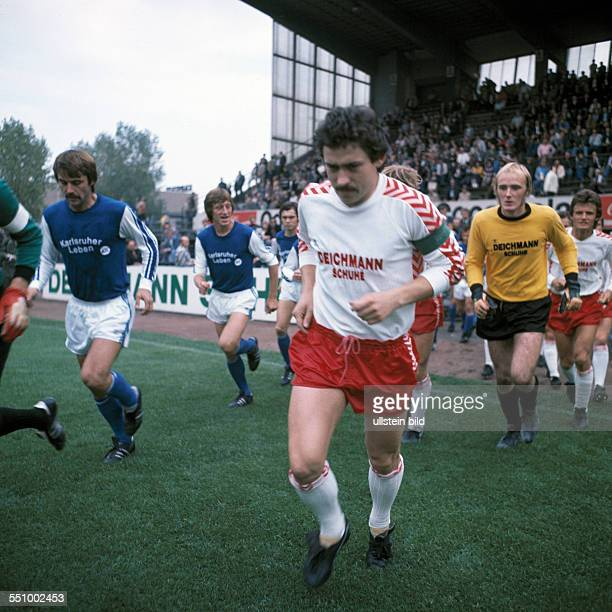 football Bundesliga 1976/1977 Georg Melches Stadium Rot Weiss Essen versus Karlsruher SC 32 runningin of the teams fltr Rainer Ulrich KarlHeinz...