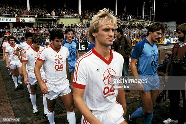 football Bundesliga 1983/1984 Grotenburg Stadium FC Bayer 05 Uerdingen versus Bayer 04 Leverkusen 21 runningin of the teams fltr Dieter Bast BumKun...