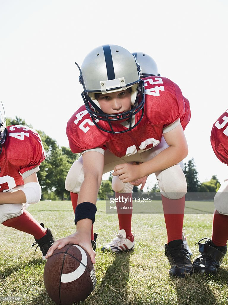 Football center preparing to snap football : Stock Photo