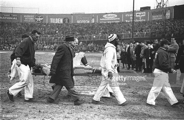 Football championship Baltimore Colts Gino Marchetti with broken ankle injury getting carried off field on stretcher by trainers and coaches during...