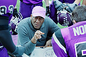 Football coach crouching, talking to team in huddle