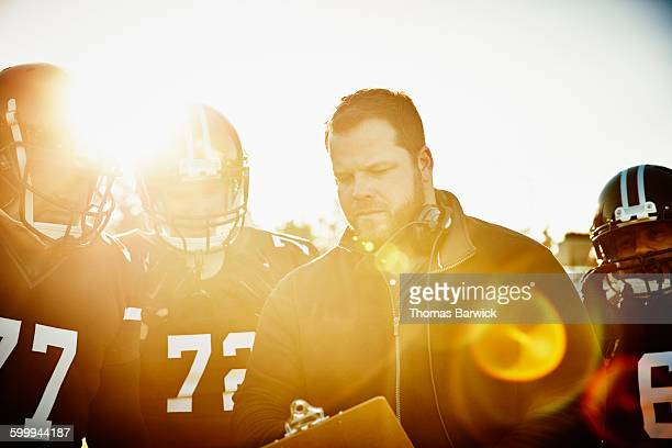 Football coach going over play with players