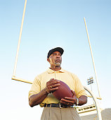 Football coach holding football, standing in front of goal post