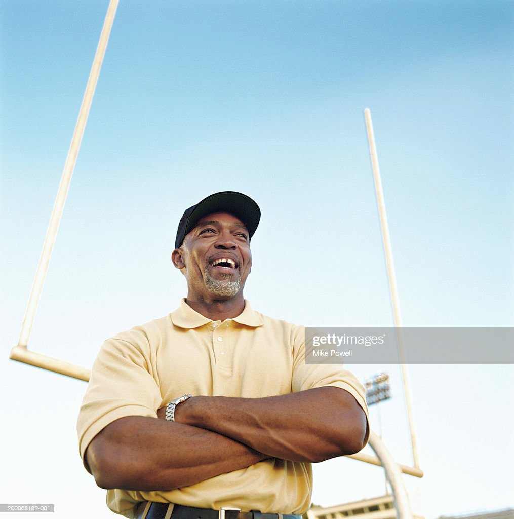 Football coach laughing, standing in front of goal post, low angle : Stock Photo