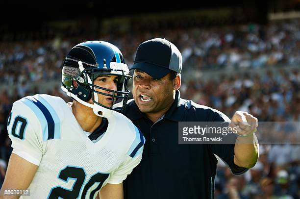 Football coach motivating player on sideline