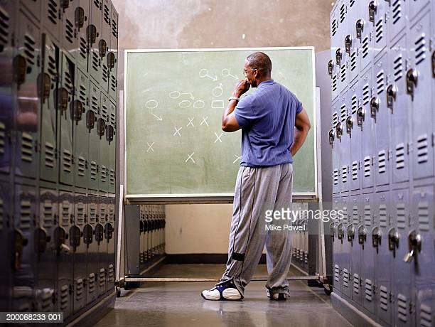Football coach standing in locker room, looking at play on chalkboard