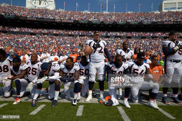 Denver Broncos Garett Bolles and Derek Wolfe with teammates kneeling and linking arms in a show of solidarity during the National Anthem before game...