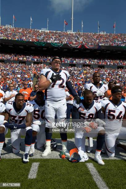 Denver Broncos Garett Bolles with teammates kneeling and linking arms in a show of solidarity during the National Anthem before game vs Buffalo Bills...