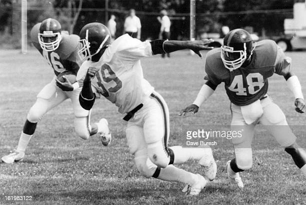 JUL 24 1984 JUL 25 1984 Football Denver Broncos Jesse Myles gets turned completely around and is able to get a shot at the ball carrier