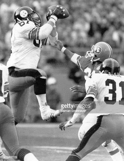 DEC 30 1984 DEC 31 1984 Football Denver Broncos Pittsburg nosetackle Gary Dunn picks off a wounded duck John Elway pass and sets up to return it