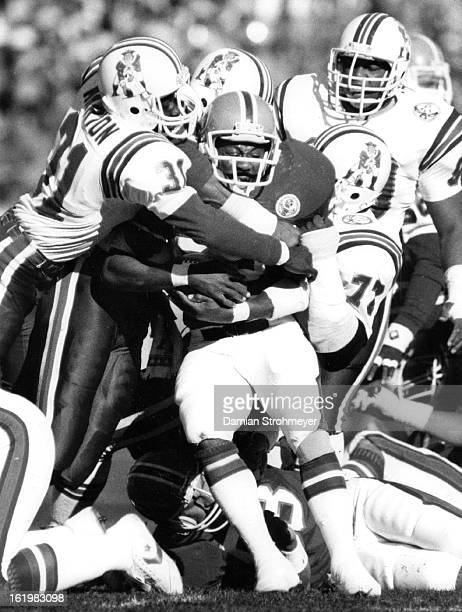 NOV 4 1984 NOV 5 1984 Football Denver Broncos Sammy Winder drew a horde of Patriot defenders on this carry in the first half
