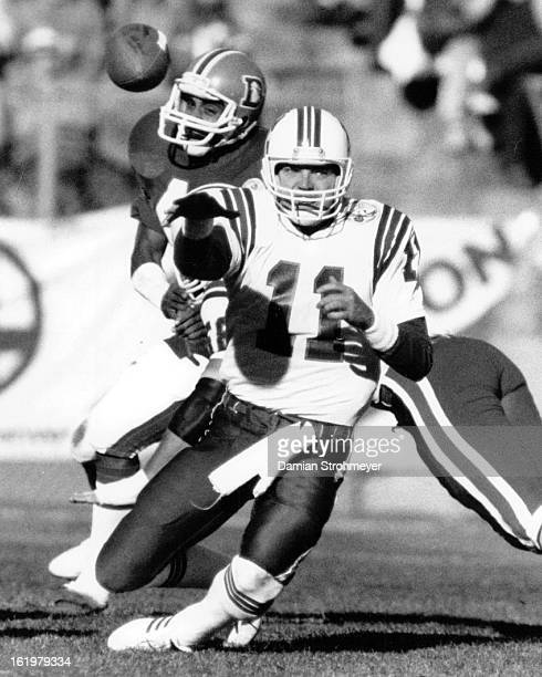 NOV 4 1984 NOV 5 1984 Football Denver Broncos Tony Eason unloads a pass while falling to his knees in the first half Dennis Smith is on the rush for...